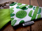 Reversible over the collar dog bandana with different cacti on a white background on the front, and a light green with white polka dot pattern on the back.