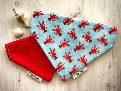 Reversible over the collar dog bandana with red lobsters and white polka dots on a light blue background on the front, and dark red with lighter red circles on the back.