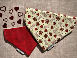 Over the collar reversible dog bandana with red hearts, brown paws, and tan bones on a cream background on one side with a shades of red fabric on the reverse