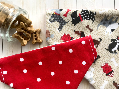 Reversible over the collar dog bandana with shades of different dogs and their bones and fire hydrants on the front, and a red with white polka dot pattern on the back.