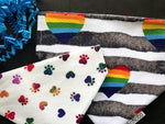 Reversible pet bandana with black stripes and rainbow hearts on one side and rainbow paw prints and hearts on a white background on the other