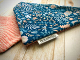 Reversible over the collar dog bandana with a pattern of blue, peach, and white flowers, acorns, and butterflies on the front, with wavy patterns of peach on the back.