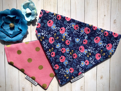 Reversible dog bandana with pink and blue flowers on a dark blue background on one side and gold polka dots on a pink background on the reverse