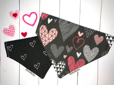Reversible over the collar dog bandana with white hearts on a black background on one side and a black background with pink, grey, and white doodled hearts on the other side