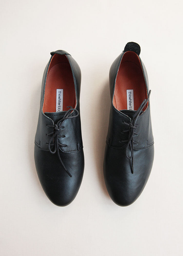 classic black leather daerby shoes from top on cream background