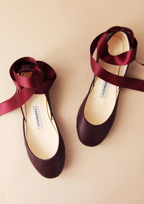 bordeaux leather ballet flats with matching satin ankle straps on light background in front view