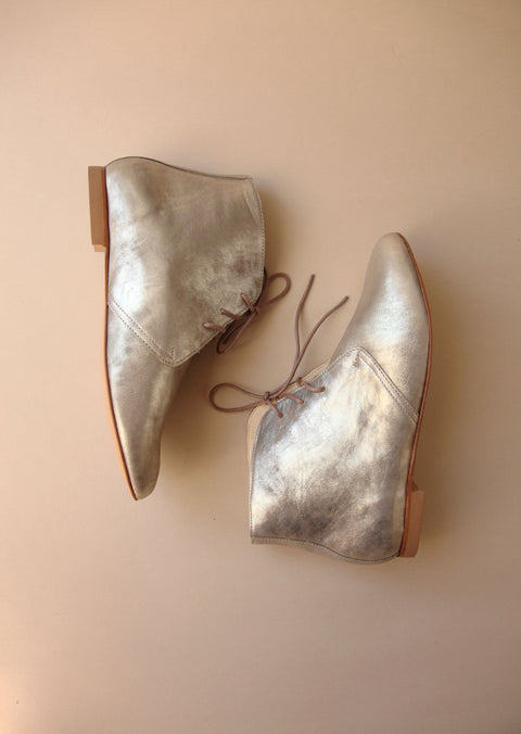 shiny silver ankle boots with brown laces from side view