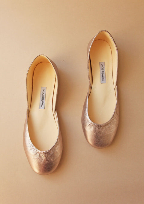 blush gold ballerina shoes in top view with blush background