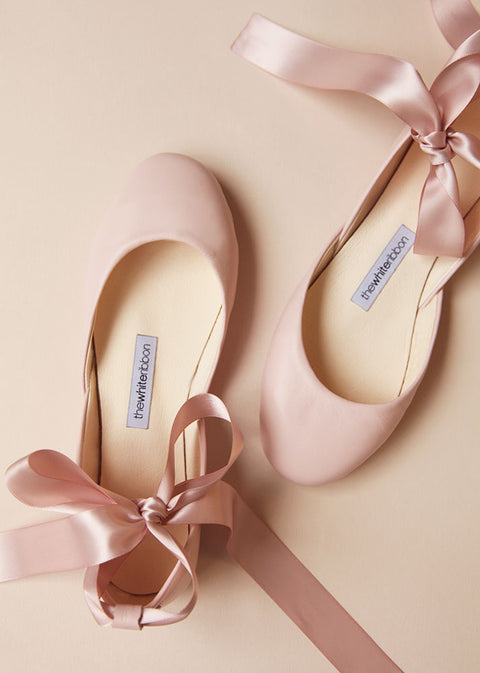 top view of a pair of blush leather ballerinas with blush satin ribbons