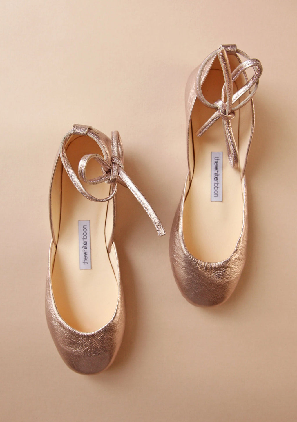 Blush gold ballet flats with leather ankle ribbons