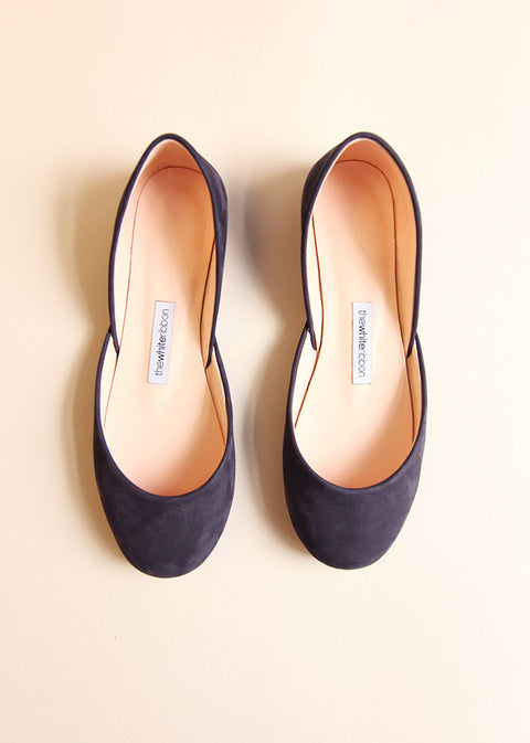 dark blue soft leather ballet flats in top view with cream background