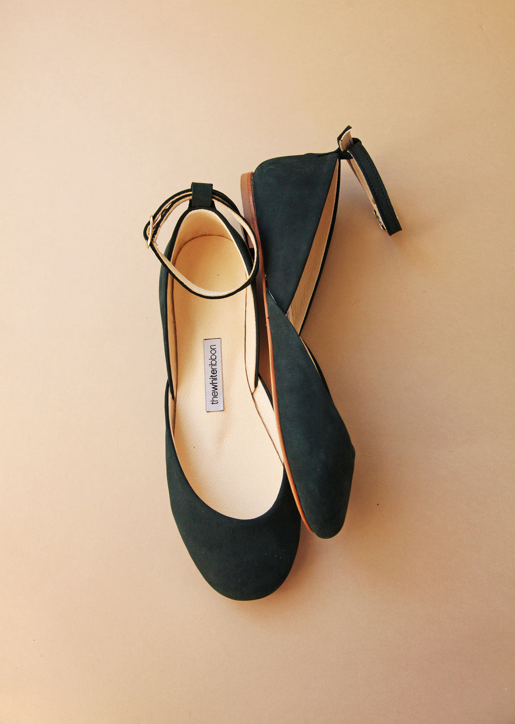dark green ballet flats with matching ankle straps from side and top on pastel background