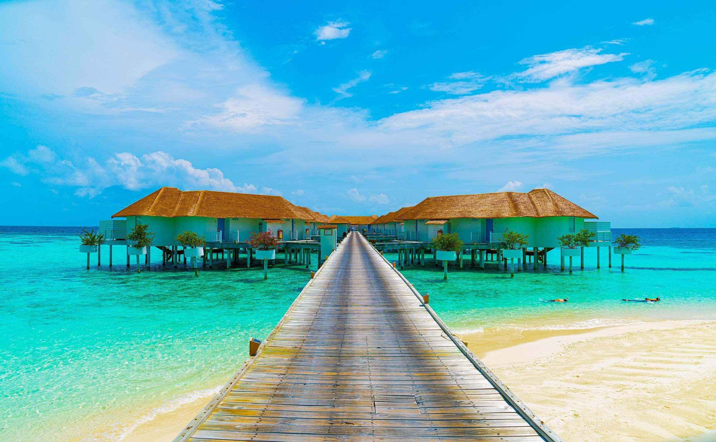 Huts over water with walkway and emerald water
