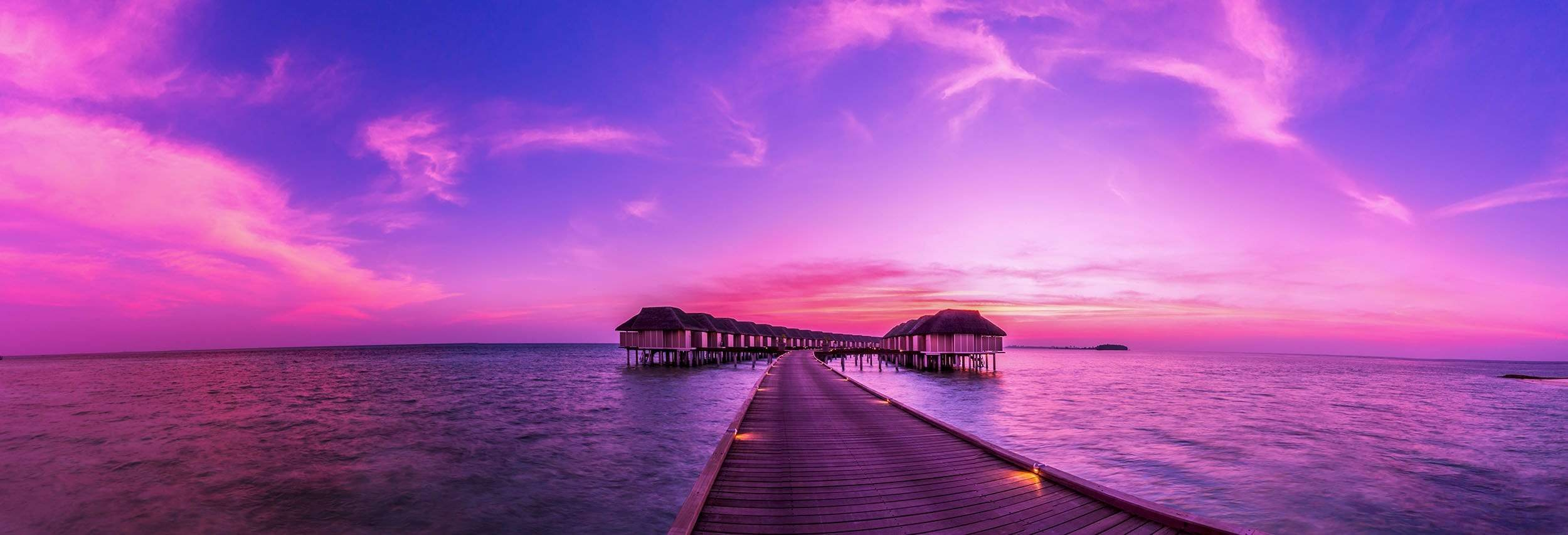 Sunset on Maldives island pier to water villas resort