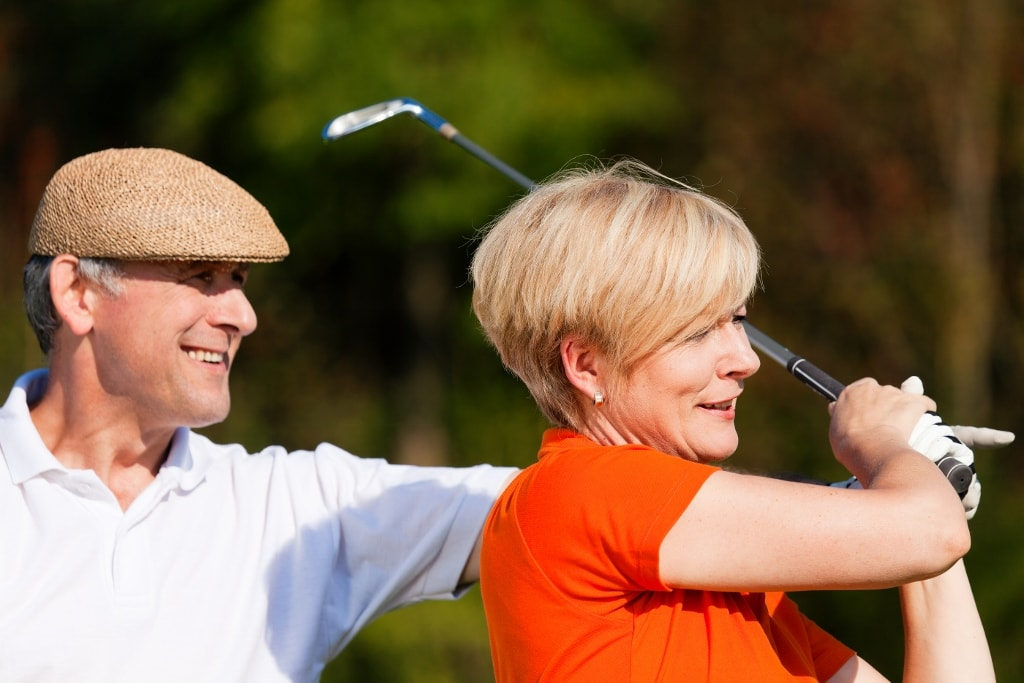 senior couple playing golf on a summer afternoon, the male partn