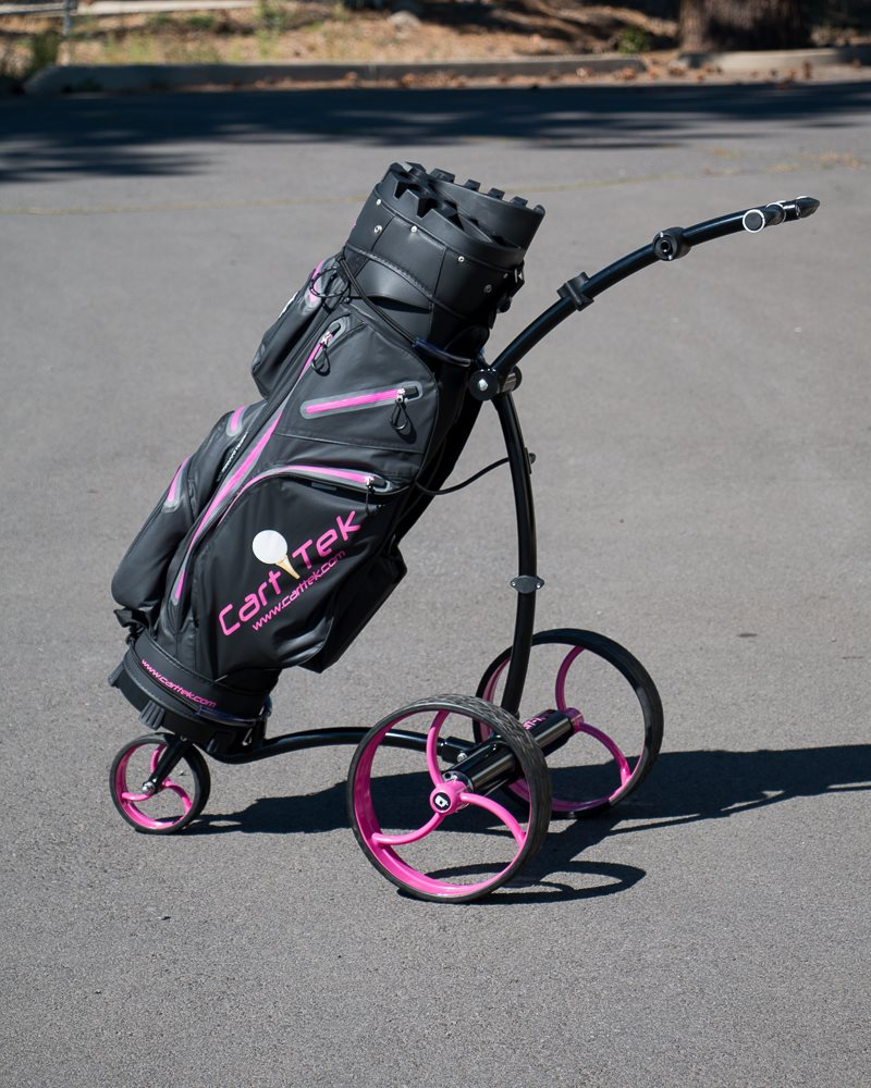 Black Cart-Tek GRI-975Li battery powered electric golf trolley with pink wheels and golf bag