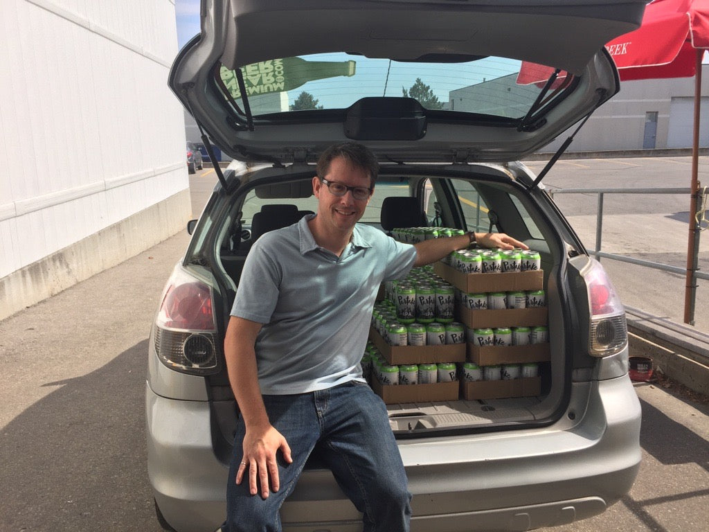 Ted sitting next to a car trunk full of Partake IPA