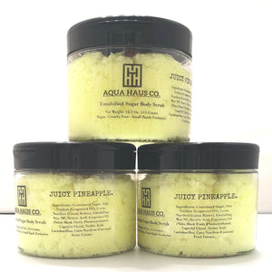 A stack of Juicy Pineapple Emulsified Sugar Scrub tubs. Displaying the ingredients list.