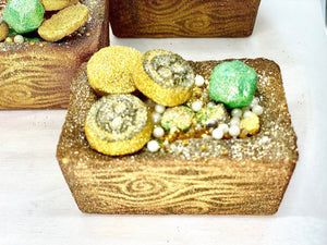 A very close up image of a Treasure Chest Bath Bomb. Full of shiny and sparkly loot: Sugar Pearls and Crystals with hand painted mini Mictlan Medallions and Gems. Enjoy your very own trunk of Treasure that soothes and nourishes your skin.- AQUA HAUS CO.
