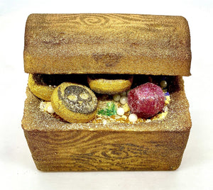 This is a up close front facing image of a half open Treasure Chest Bath Bomb showing off mini Mictlan, Pearls and Jewel treasure! Hand painted in a Wood Grain motif on the outside. Contains surprise color burst embeds.  The Treasure Chest Bath Bomb is two pieces including the trunk and lid. Scented in the absolutely delicious Baccarat Rouge 540 with a hint of Caribbean Coconut.