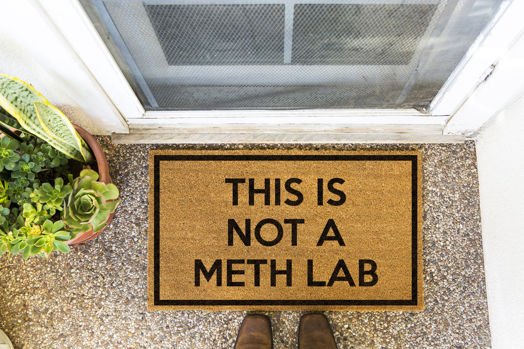Brown doormat on a nice looking porch with shoes at the base of the mat.  The brown doormat has a black border and has black centered text that reads This Is Not A Meth Lab