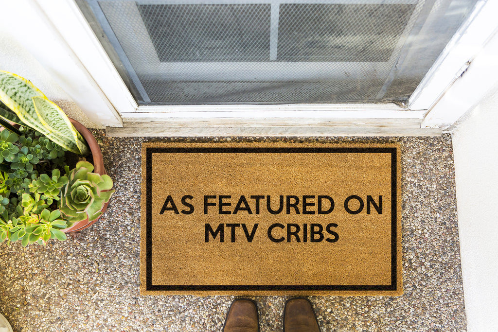 Brown doormat on a nice looking porch with shoes at the base of the mat.  The brown doormat has a black border and has black centered text that reads As Featured on MTV Cribs