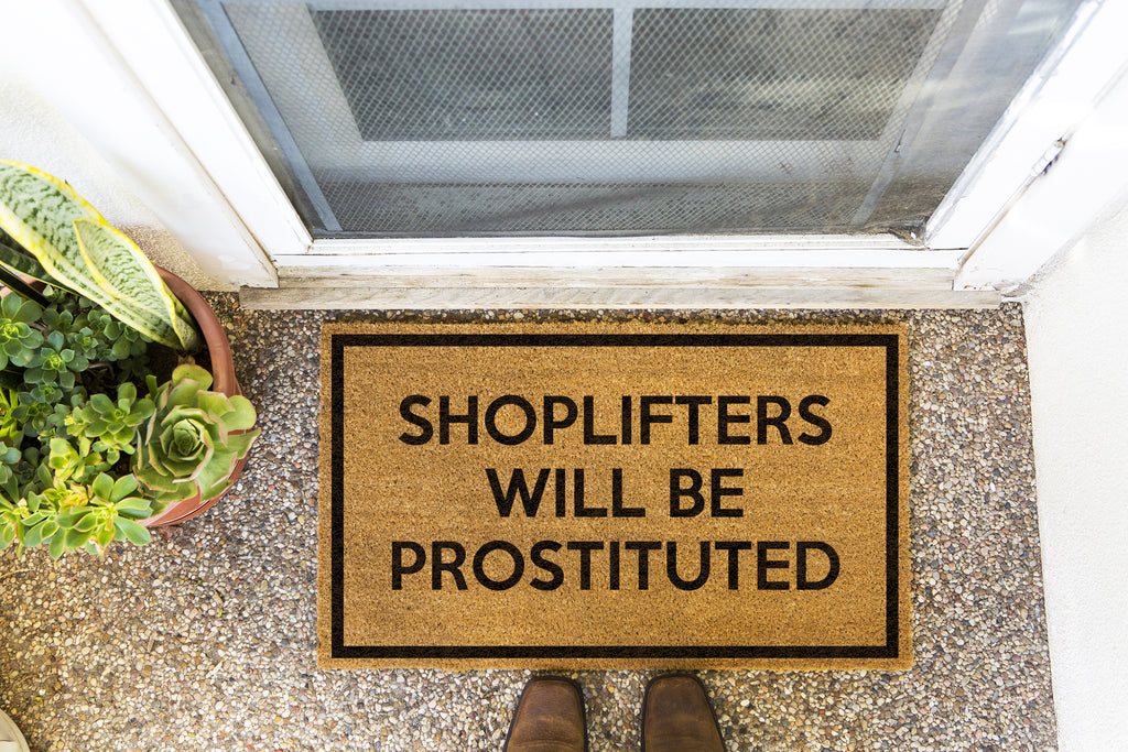 Brown doormat on a nice looking porch with shoes at the base of the mat.  The brown doormat has a black border and has black centered text that reads Shoplifters Will Be Prostituted