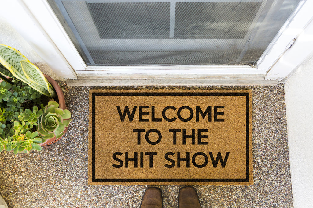 Brown doormat on a nice looking porch with shoes at the base of the mat.  The brown doormat has a black border and has black centered text that reads Welcome To The Shit Show