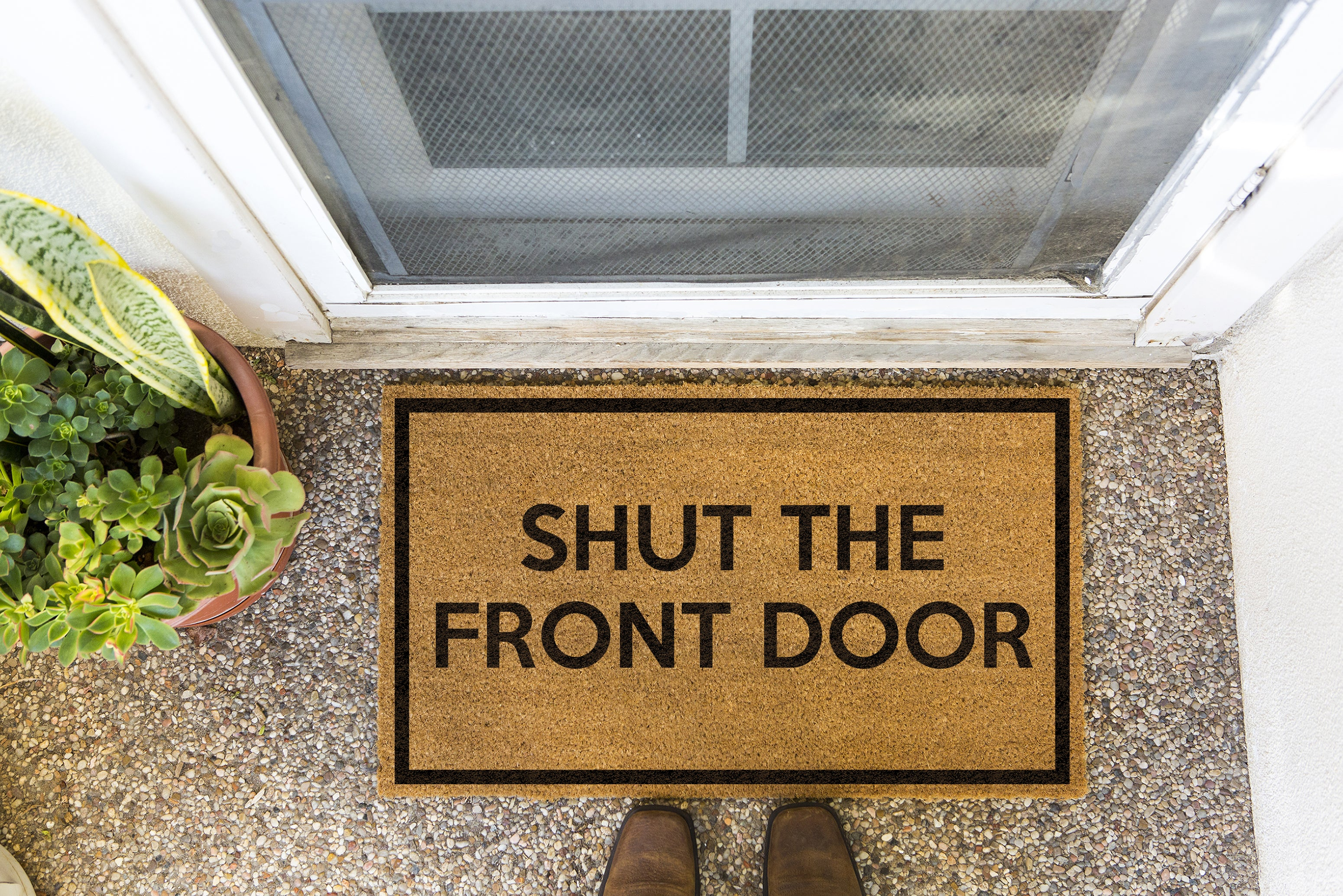 Brown doormat on a nice looking porch with shoes at the base of the mat.  The brown doormat has a black border and has black centered text that reads Shut The Front Door