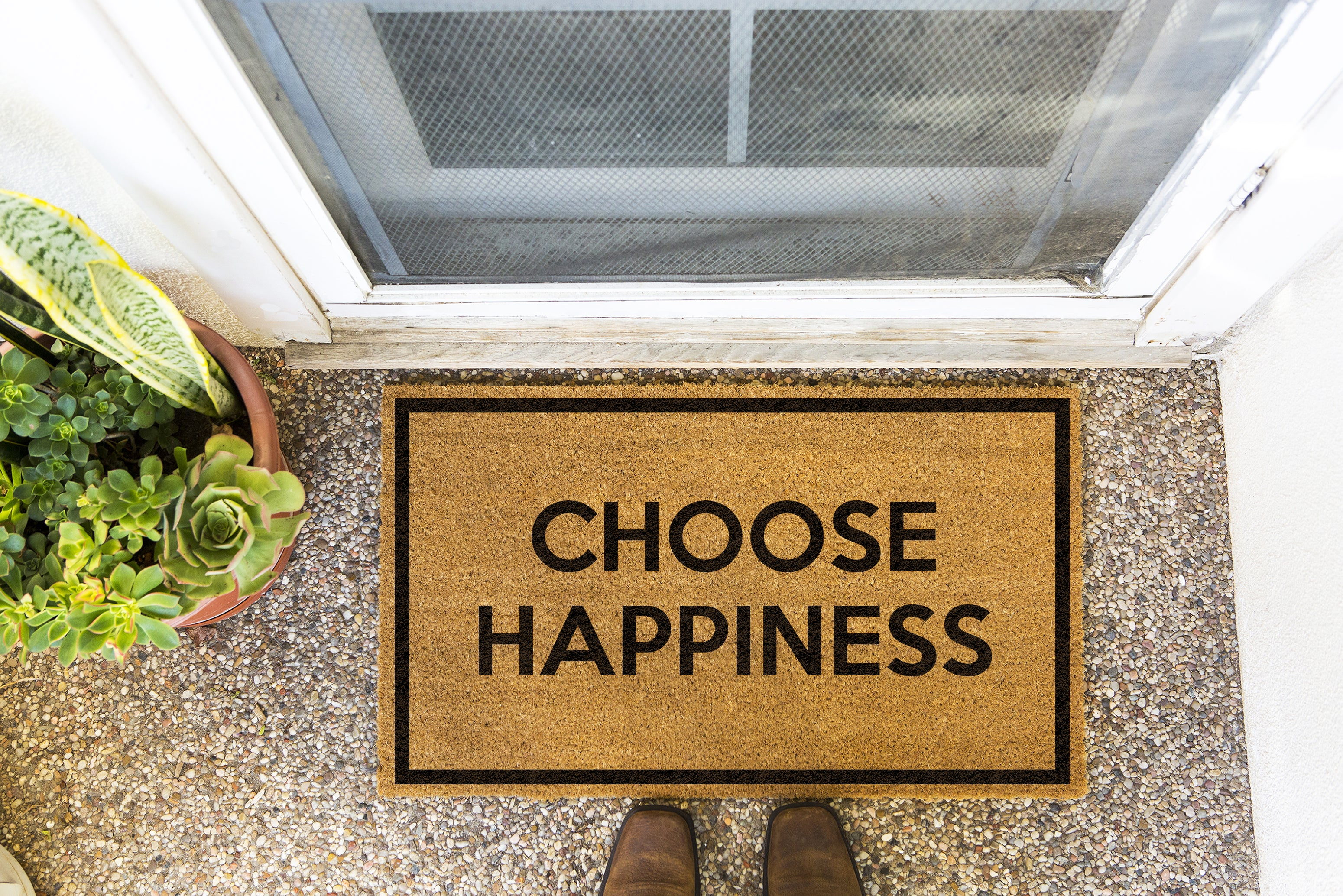 Brown doormat on a nice looking porch with shoes at the base of the mat.  The brown doormat has a black border and has black centered text that reads Choose Happiness