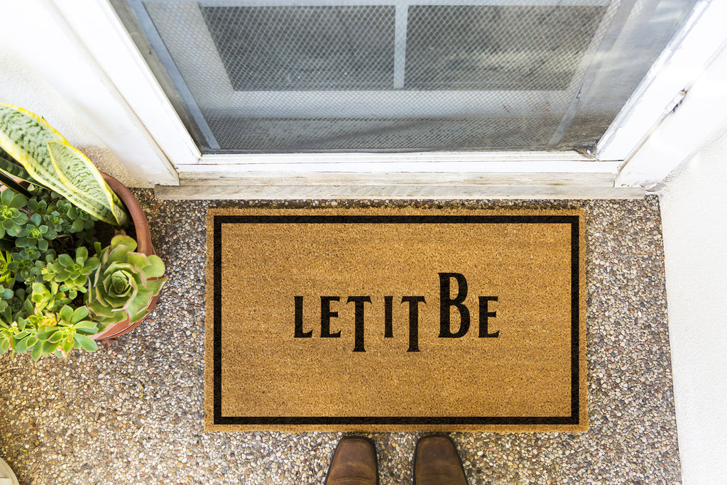 Brown doormat on a nice looking porch with shoes at the base of the mat.  The brown doormat has a black border and has black centered text that reads Let It Be