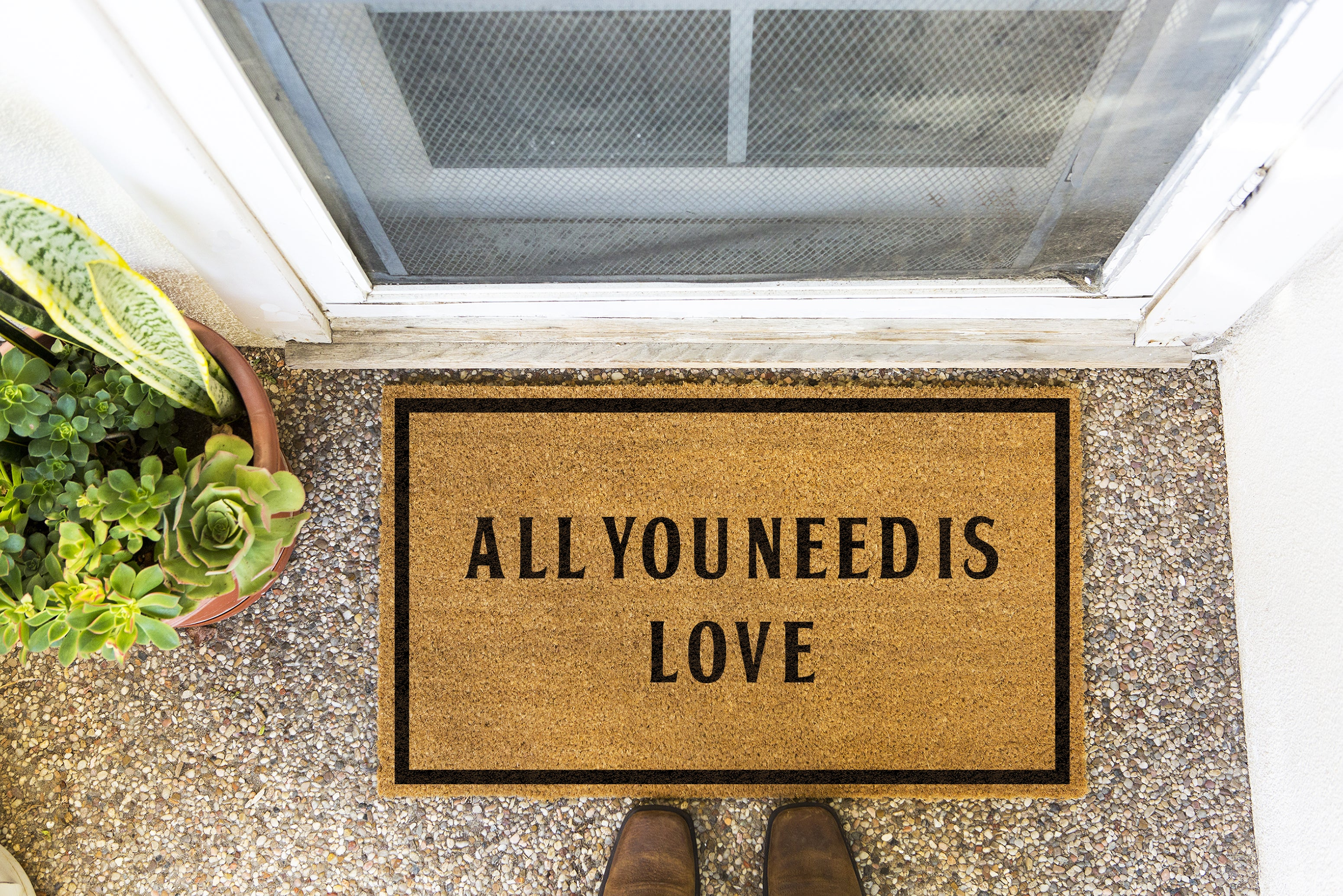 Brown doormat on a nice looking porch with shoes at the base of the mat.  The brown doormat has a black border and has black centered text that reads All You Need Is Love