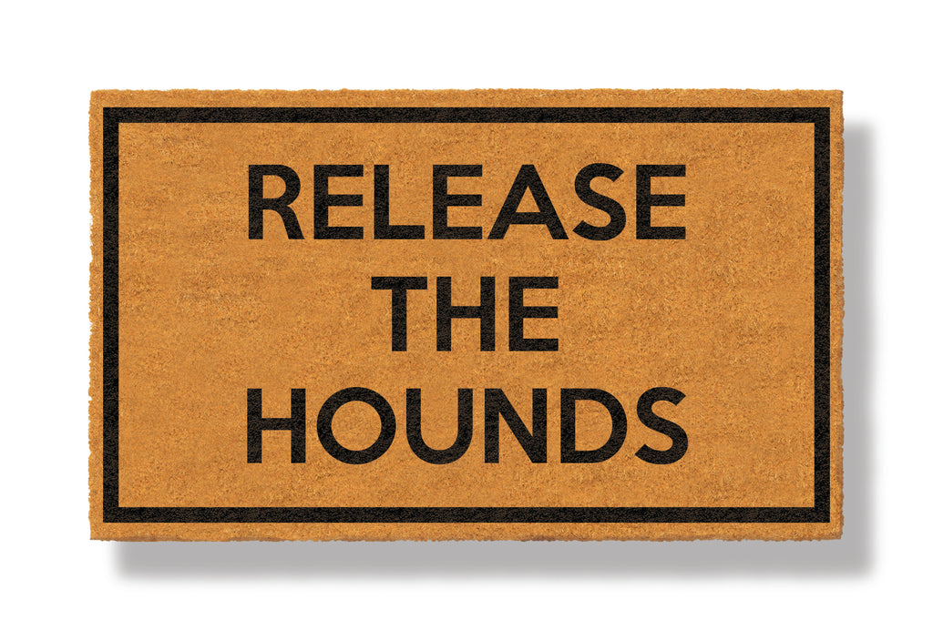 This coir welcome mat is a funny doormat on a white background with a drop shadow. The brown doormat has a black border and has black centered text that reads Release The Hounds.