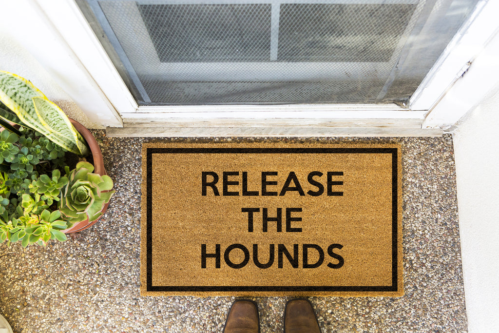 Brown doormat on a nice looking porch with shoes at the base of the mat.  The brown doormat has a black border and has black centered text that reads Release The Hounds