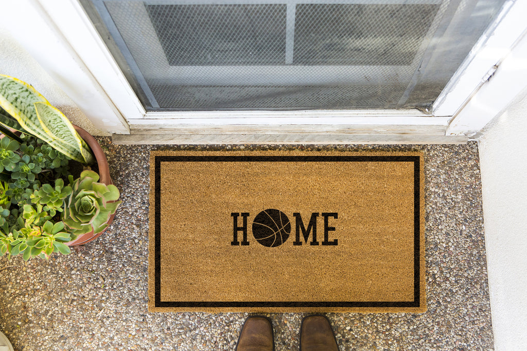 Brown doormat on a nice looking porch with shoes at the base of the mat.  The brown doormat has a black border and has black centered text that reads Home