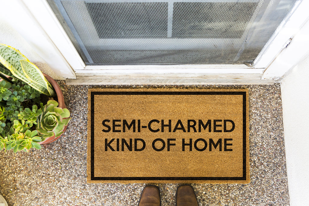 Brown doormat on a nice looking porch with shoes at the base of the mat.  The brown doormat has a black border and has black centered text that reads Semi-Charmed Kind Of Home