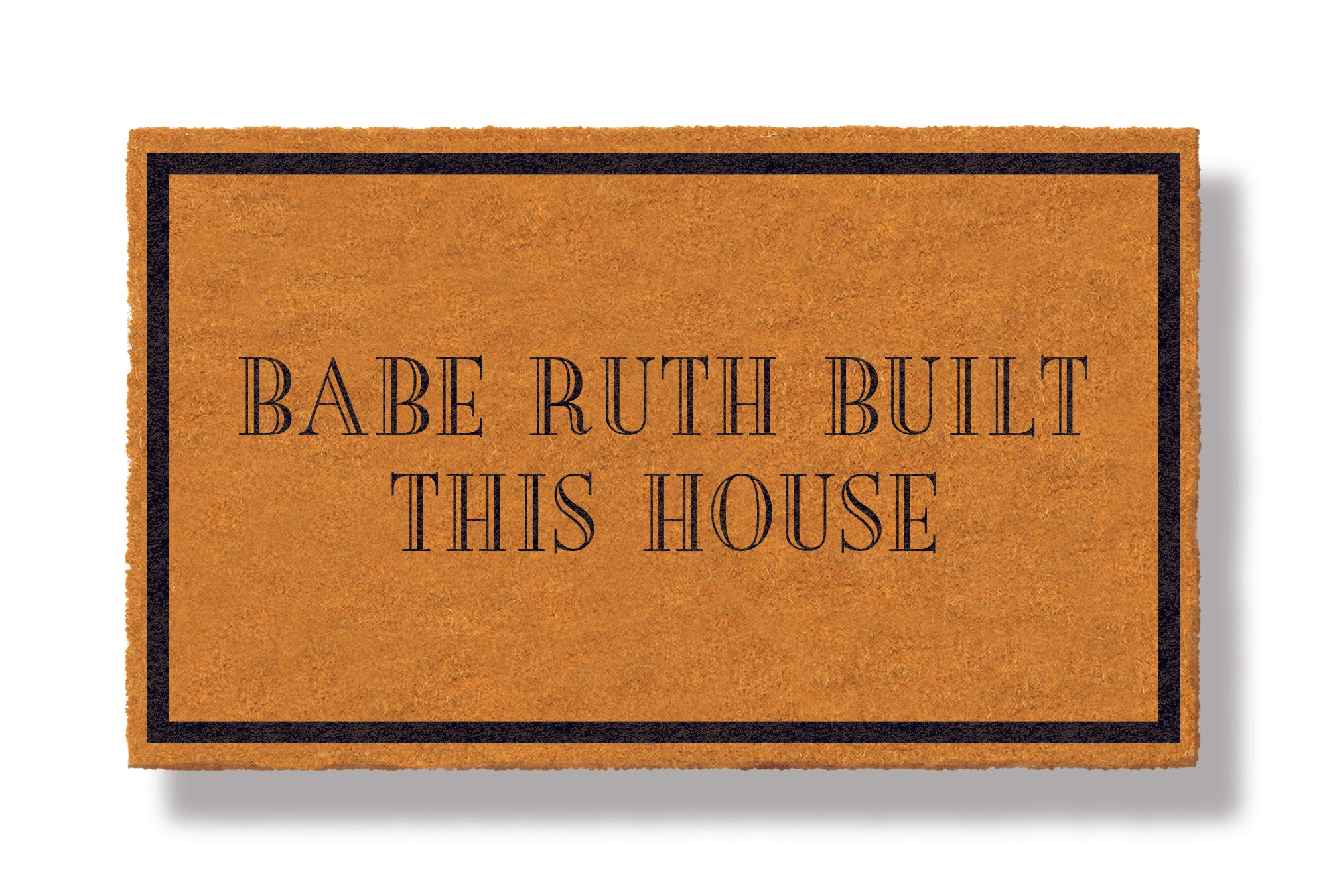 This coir welcome mat is a funny doormat on a white background with a drop shadow. The brown doormat has a black border and has black centered text that reads Babe Ruth Built This House.