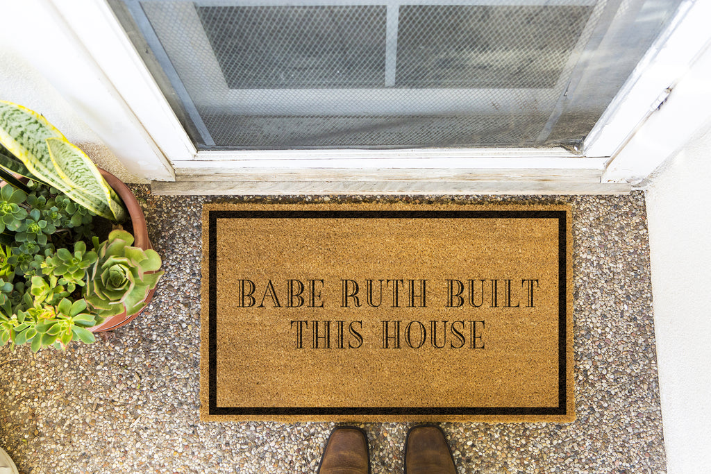 Brown doormat on a nice looking porch with shoes at the base of the mat.  The brown doormat has a black border and has black centered text that reads Babe Ruth Built This House