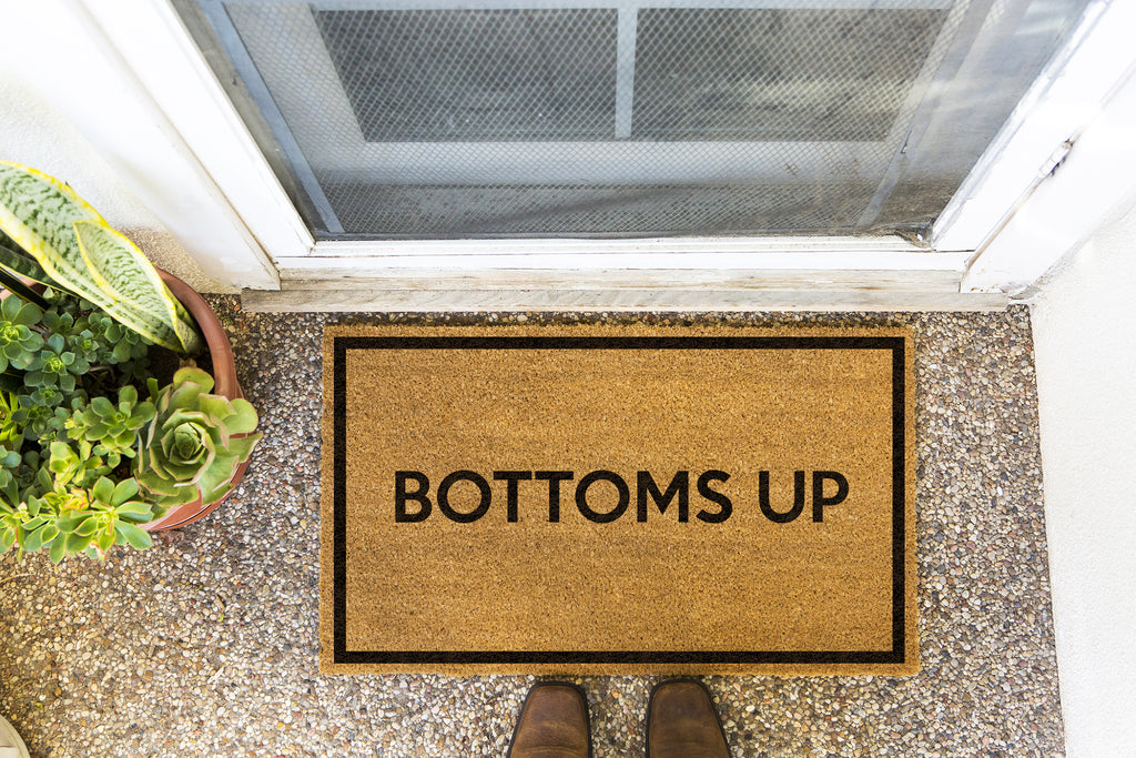 Brown doormat on a nice looking porch with shoes at the base of the mat.  The brown doormat has a black border and has black centered text that reads Bottoms Up