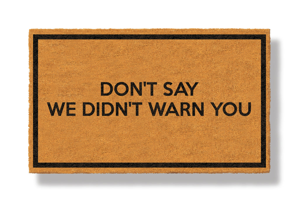 This coir welcome mat is a funny doormat on a white background with a drop shadow. The brown doormat has a black border and has black centered text that reads Don't Say We Didn't Warn You.