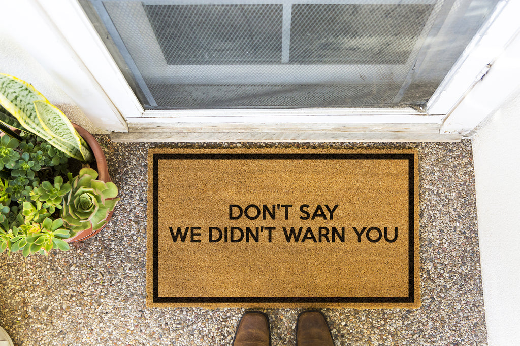 Brown doormat on a nice looking porch with shoes at the base of the mat.  The brown doormat has a black border and has black centered text that reads Don't Say We Didn't Warn You