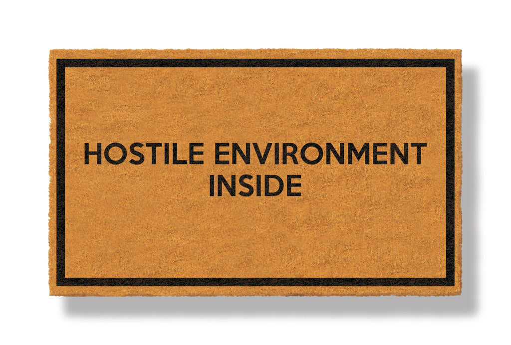 This coir welcome mat is a funny doormat on a white background with a drop shadow. The brown doormat has a black border and has black centered text that reads Hostile Environment Inside.