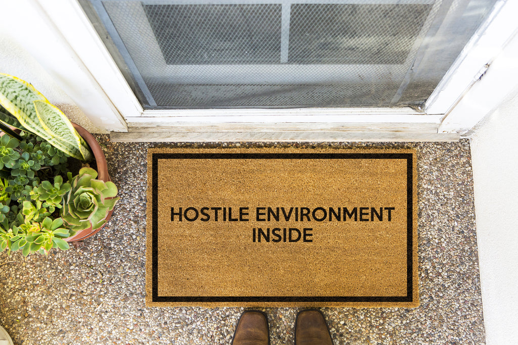 Brown doormat on a nice looking porch with shoes at the base of the mat.  The brown doormat has a black border and has black centered text that reads Hostile Environment Inside