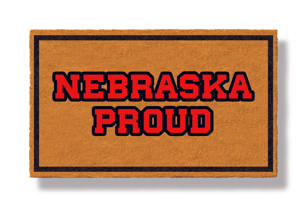 This coir welcome mat is a funny doormat on a white background with a drop shadow. The brown doormat has a black border and has black centered text that reads Nebraska Proud.