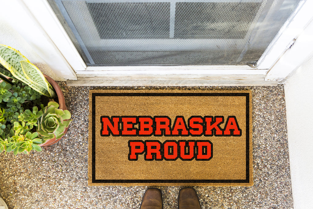 Brown doormat on a nice looking porch with shoes at the base of the mat.  The brown doormat has a black border and has black centered text that reads Nebraska Proud