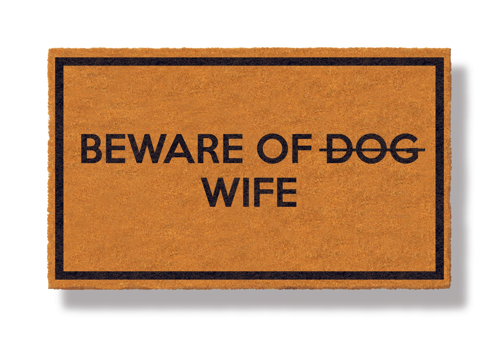 This coir welcome mat is a funny doormat on a white background with a drop shadow. The brown doormat has a black border and has black centered text that reads Beware of Dog strikethrough Wife.