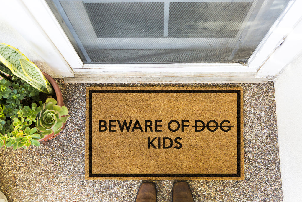 Brown doormat on a nice looking porch with shoes at the base of the mat. The brown doormat has a black border and has black centered text that reads Beware of Dog strikethrough Kids