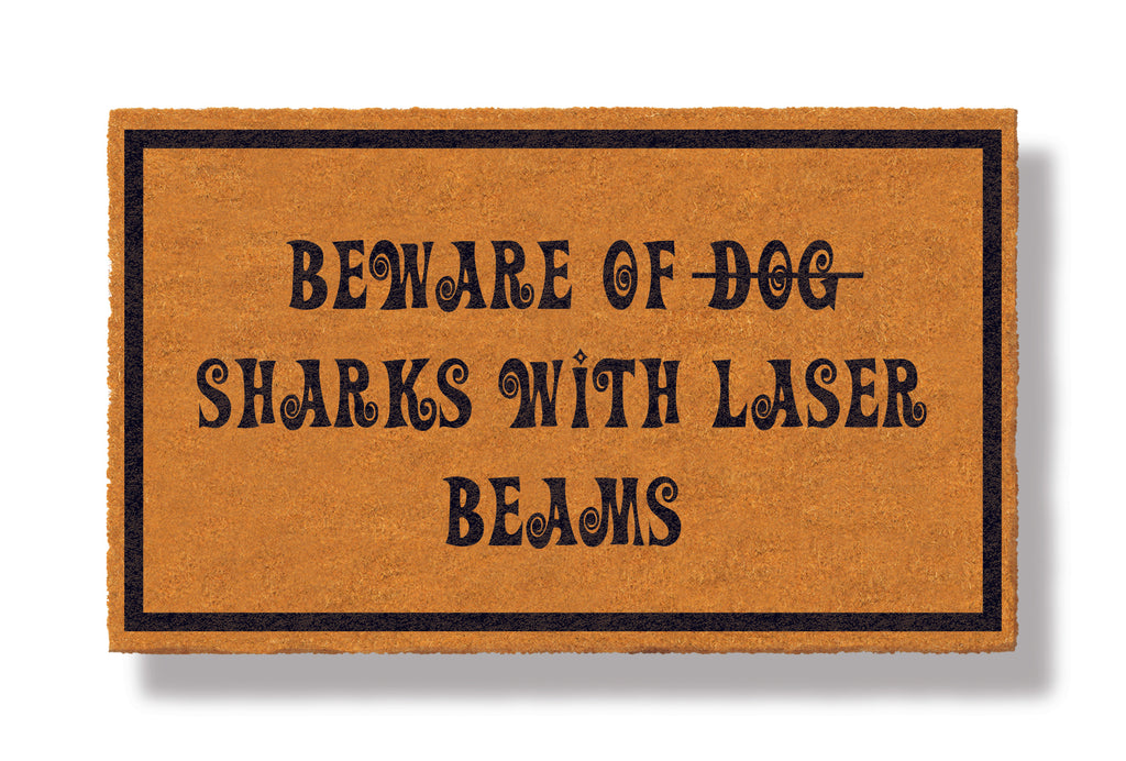 This coir welcome mat is a funny doormat on a white background with a drop shadow. The brown doormat has a black border and has black centered text that reads Beware of Dog strikethrough Sharks With Laser Beams.