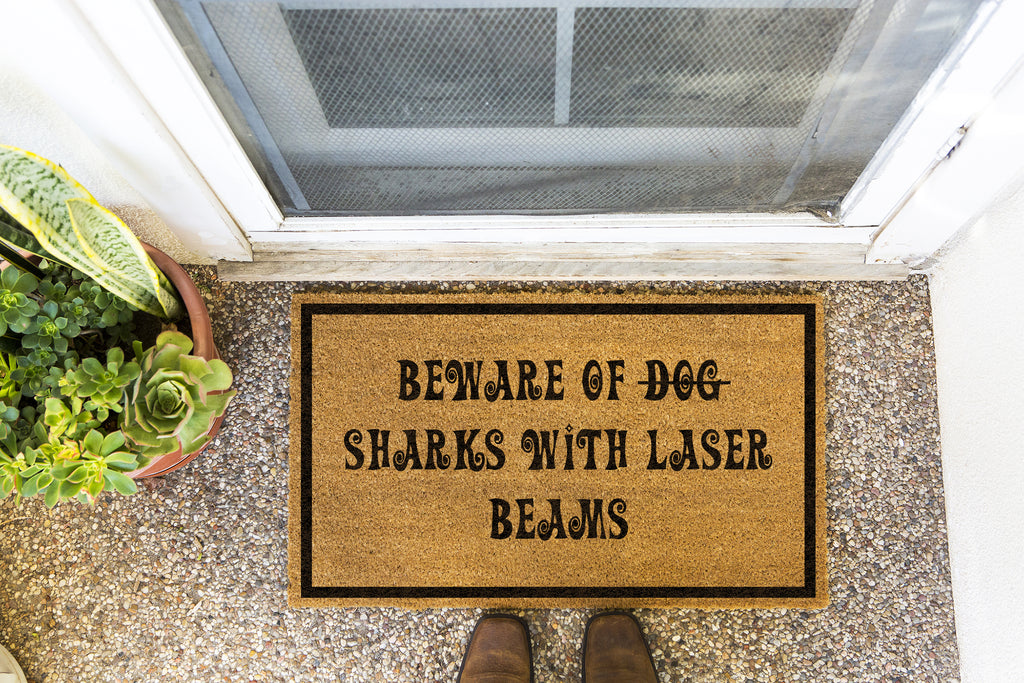 Brown doormat on a nice looking porch with shoes at the base of the mat. The brown doormat has a black border and has black centered text that reads Beware of Dog strikethrough Sharks With Laser Beams