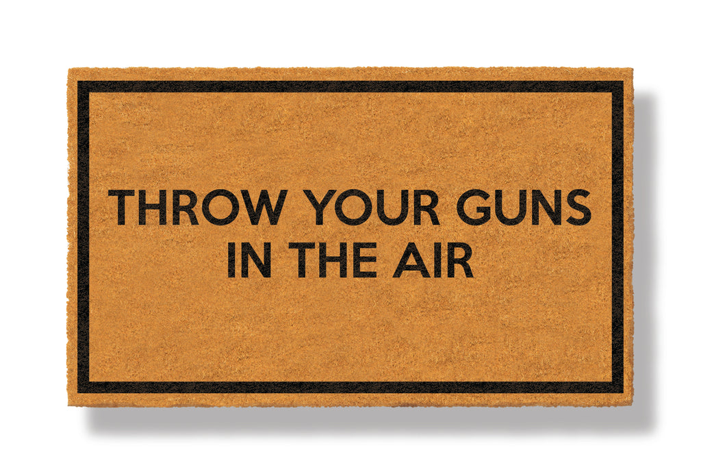 This coir welcome mat is a funny doormat on a white background with a drop shadow. The brown doormat has a black border and has black centered text that reads Throw Your Guns In The Air.
